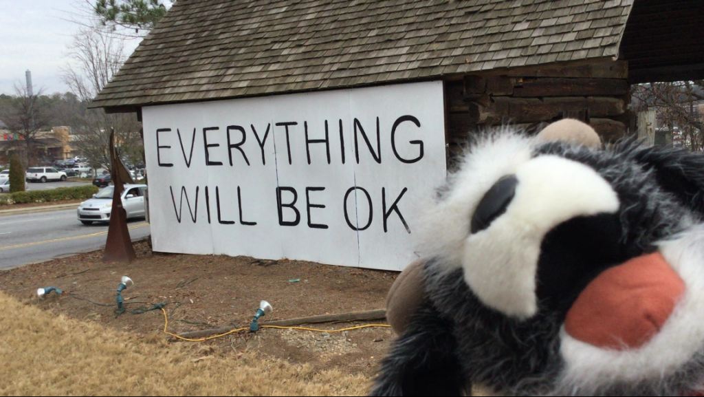 "Goat puppet Buster Bleaton smiles widely in front of a barn painted with the words ""Everything Will Be OK."""
